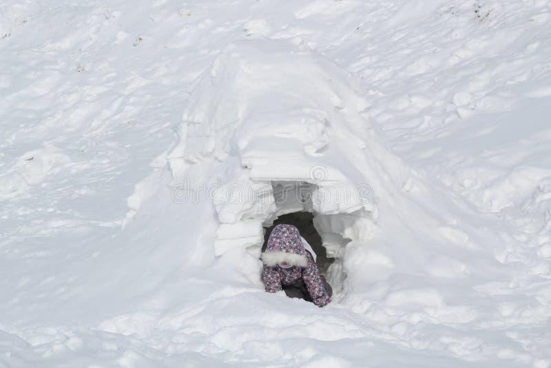 Το παιδί αναρριχείται από τη σπηλιά χιονιού - κατοικία Inuit, παγοκαλύβα στοκ φωτογραφία με δικαίωμα ελεύθερης χρήσης
