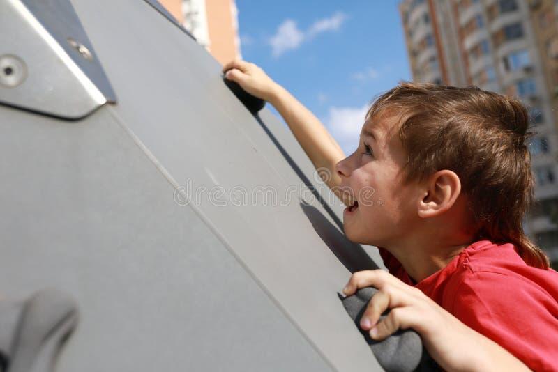 Το παιδί αναρριχείται στον τοίχο στοκ φωτογραφίες