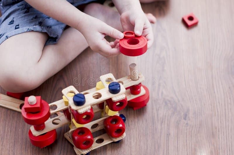 Το παιδί βάζει ξύλινο κόκκινο shim στο μπουλόνι στοκ εικόνα με δικαίωμα ελεύθερης χρήσης