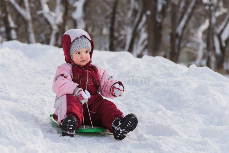 Το παιδί γλιστρά κάτω από έναν λόφο σε ένα έλκηθρο στοκ φωτογραφίες με δικαίωμα ελεύθερης χρήσης
