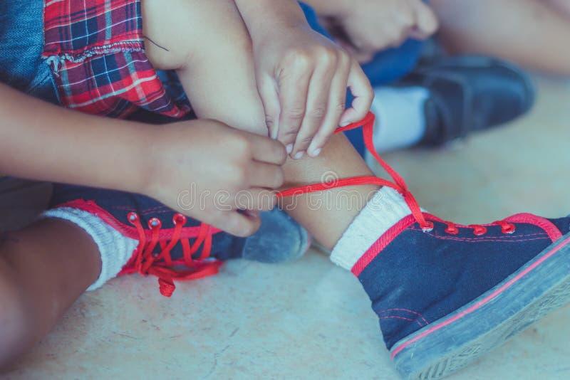 Το παιδί δένει τις δαντέλλες παπουτσιών προτού να παρουσιάσει το στάδιο στοκ φωτογραφία με δικαίωμα ελεύθερης χρήσης