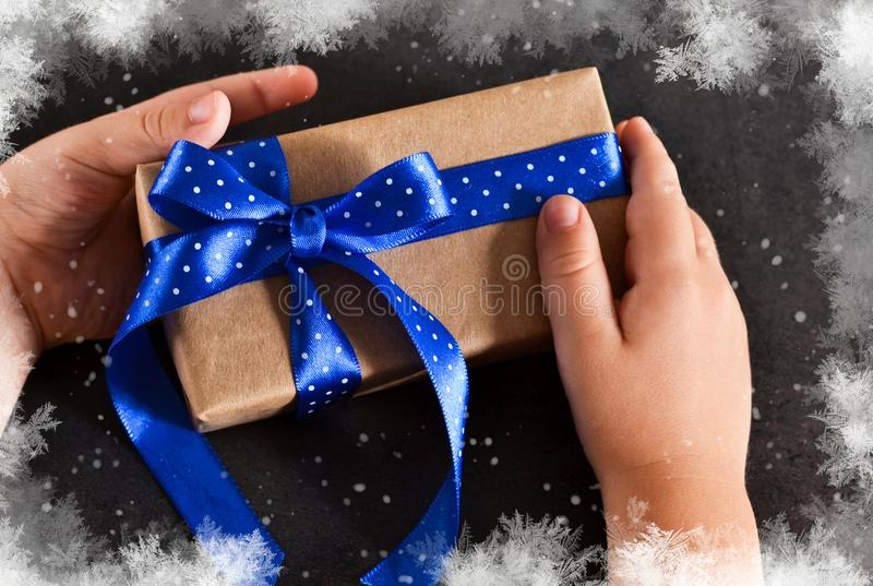 Το παιδί δίνει το δεμένο τόξο σε ένα κιβώτιο δώρων σε ένα μαύρο υπόβαθρο στοκ φωτογραφία με δικαίωμα ελεύθερης χρήσης