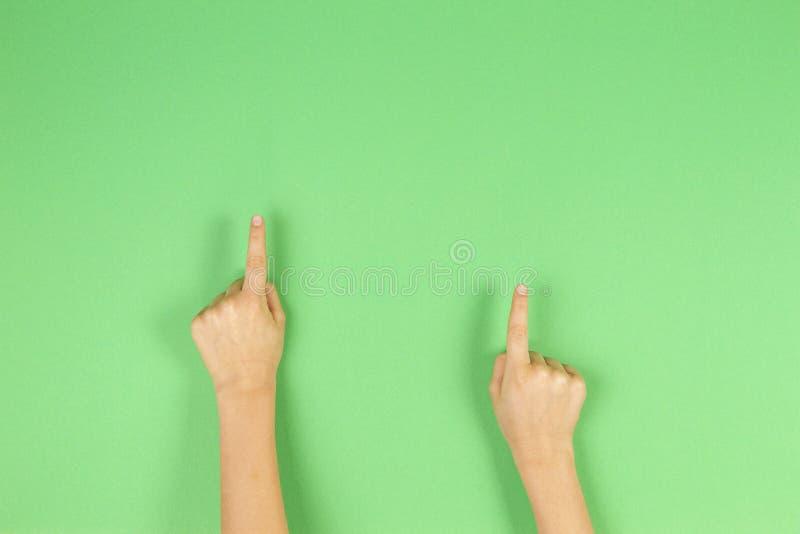 Το παιδί δίνει τα δάχτυλα δείχνοντας στο ανοικτό πράσινο υπόβαθρο στοκ εικόνα με δικαίωμα ελεύθερης χρήσης