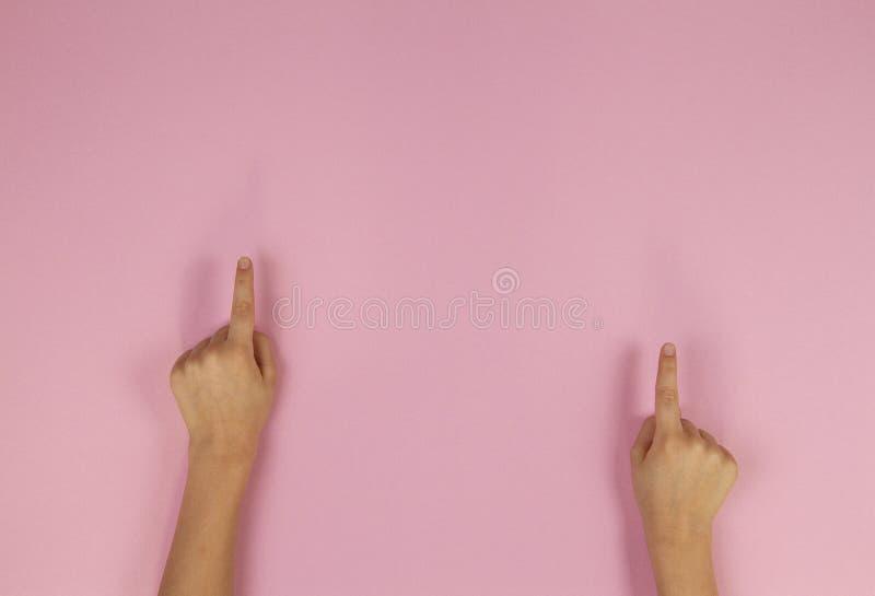 Το παιδί δίνει τα δάχτυλα δείχνοντας στο ανοικτό ροζ υπόβαθρο στοκ φωτογραφίες με δικαίωμα ελεύθερης χρήσης