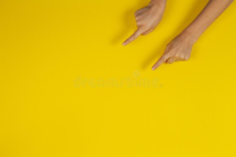 Το παιδί δίνει τα δάχτυλα δείχνοντας στο κίτρινο υπόβαθρο στοκ εικόνα