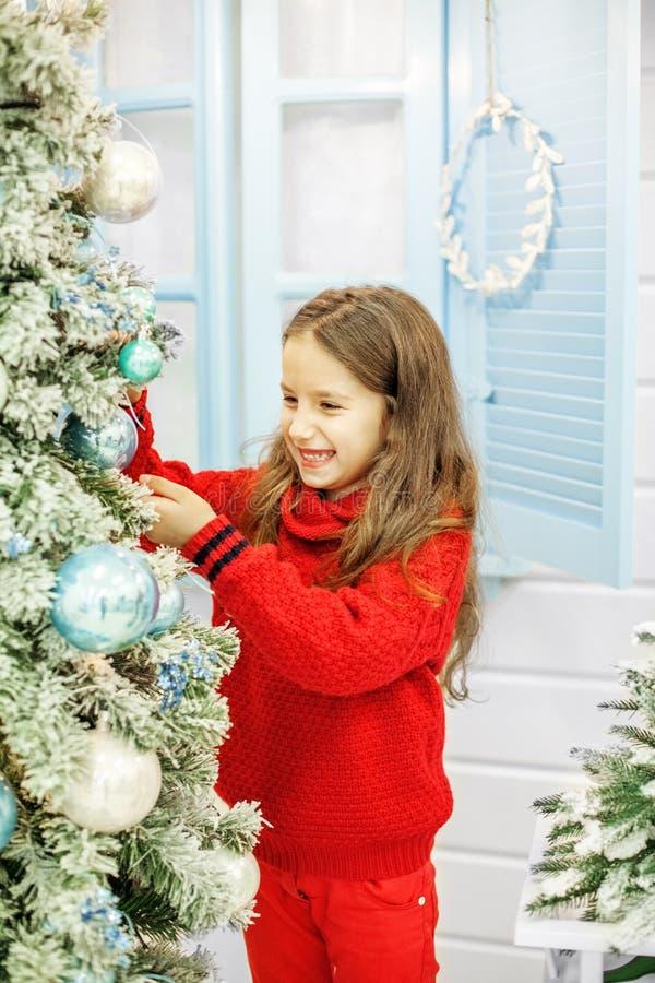 Το παιδί διακοσμεί ένα χριστουγεννιάτικο δέντρο Νέο έτος έννοιας, εύθυμο CH στοκ εικόνες