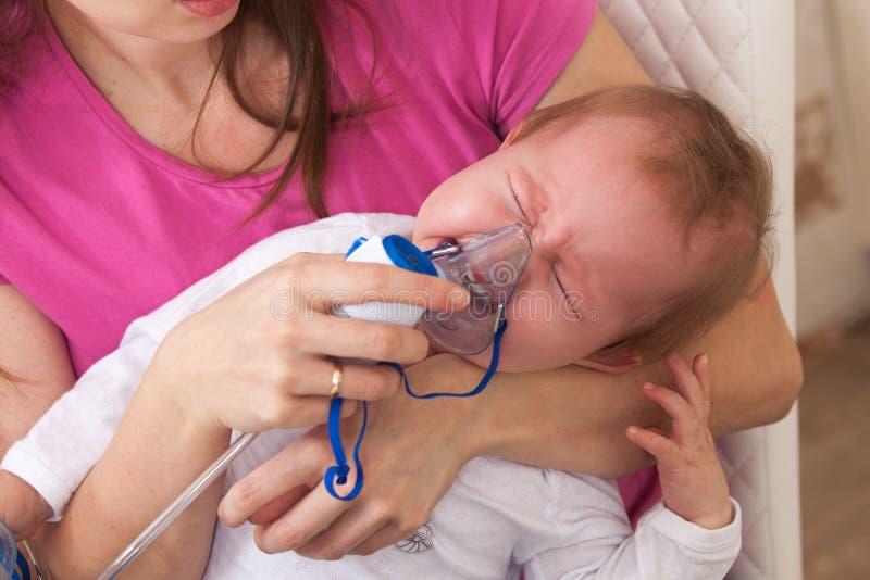 Το παιδί εισπνοής κάνει τη μαμά μωρών στοκ φωτογραφίες