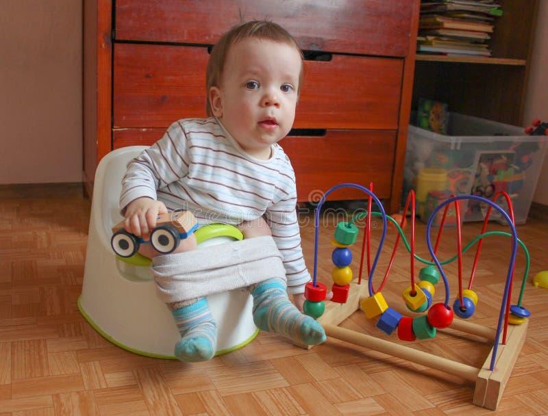 Το παιδί κάθεται σε ένα δοχείο και παίζει τα παιχνίδια Ένα εύθυμο μικρό παιδί μαθαίνει στοκ εικόνες με δικαίωμα ελεύθερης χρήσης