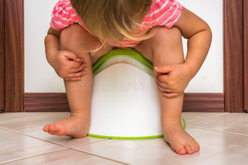 Το παιδί κάθεται στο μωρό ασήμαντο στοκ εικόνες με δικαίωμα ελεύθερης χρήσης
