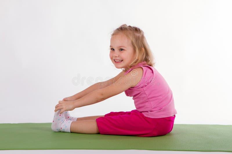 Το παιδί κάνει τις ασκήσεις άσκησης στην κουβέρτα στοκ φωτογραφίες