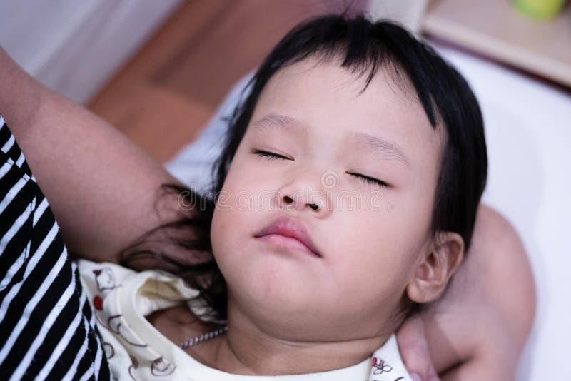 Το παιδί κοιμάται στην προστασία χεριών mom της ` s στοκ φωτογραφία