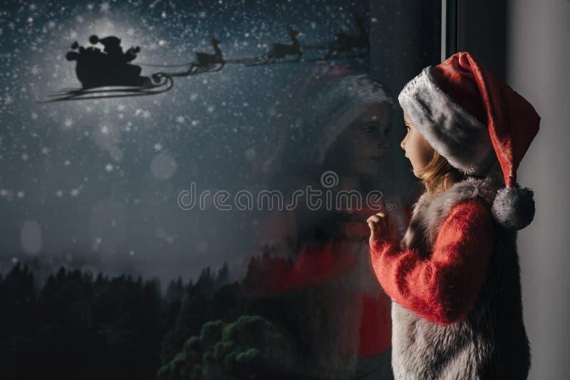 το παιδί κοιτάζει έξω από το παράθυρο την ημέρα των Χριστουγέννων στοκ φωτογραφία με δικαίωμα ελεύθερης χρήσης