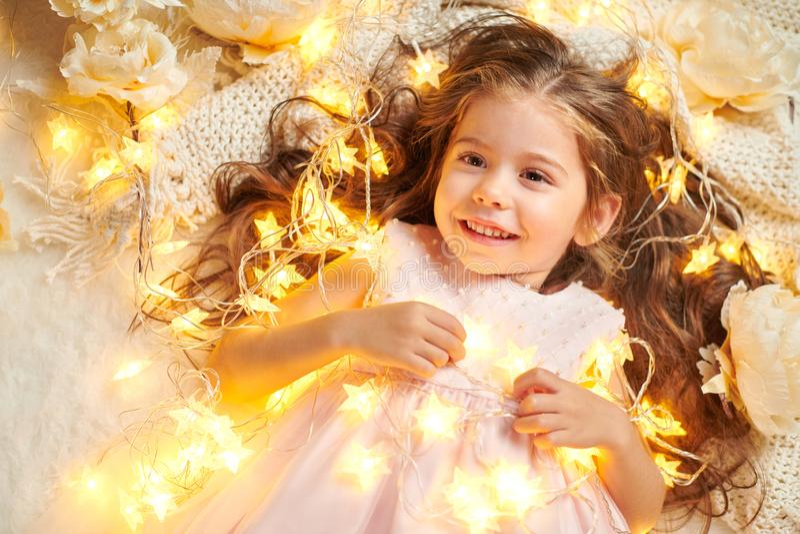 Το παιδί κοριτσιών εναπόκειται στα φω'τα Χριστουγέννων και τα λουλούδια, κινηματογράφηση σε πρώτο πλάνο προσώπου στοκ φωτογραφία με δικαίωμα ελεύθερης χρήσης