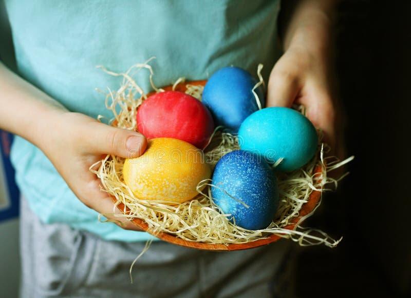 Το παιδί κρατά ένα καλάθι με τα χρωματισμένα αυγά στοκ εικόνες
