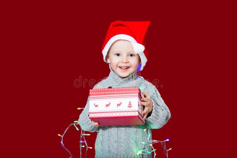 Το παιδί κρατά ένα κιβώτιο και ένα χαμόγελο δώρων Χριστουγέννων στοκ φωτογραφία με δικαίωμα ελεύθερης χρήσης
