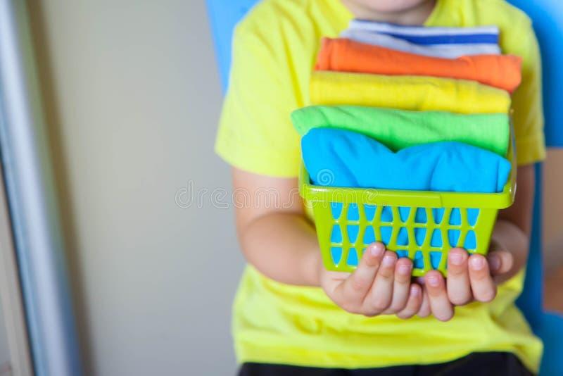Το παιδί κρατά τα πράγματά του Το αγόρι βάζει τις μπλούζες σε ένα drawe στοκ φωτογραφία με δικαίωμα ελεύθερης χρήσης