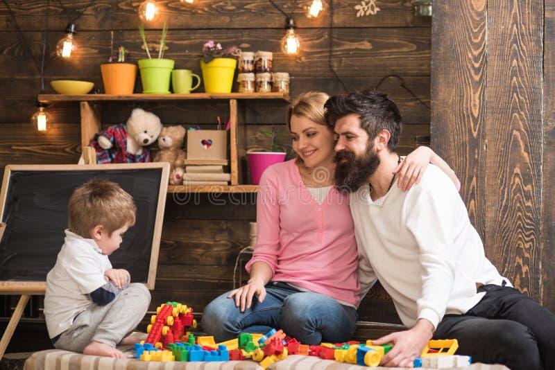 Το παιδί με το παιχνίδι γονέων με τους πλαστικούς φραγμούς, χτίζει την κατασκευή Πατέρας, μητέρα και χαριτωμένο παιχνίδι γιων με  στοκ εικόνες