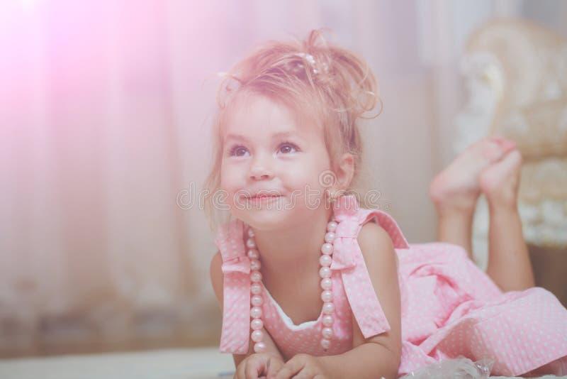 Το παιδί με το χαριτωμένο χαμόγελο στο ρόδινο φόρεμα βρίσκεται στον τάπητα στοκ εικόνες