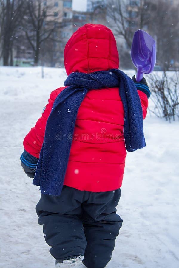 Το παιδί πηγαίνει να παίξει το φτυάρι του με το χιόνι στοκ εικόνες με δικαίωμα ελεύθερης χρήσης