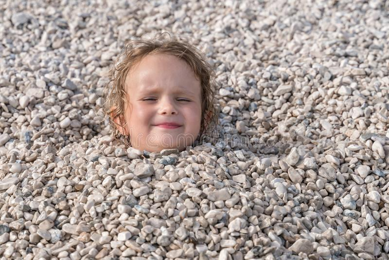 Το παιδί που θάβεται κάτω από τις πέτρες, μόνο κεφάλι μπορεί να δει στοκ φωτογραφία