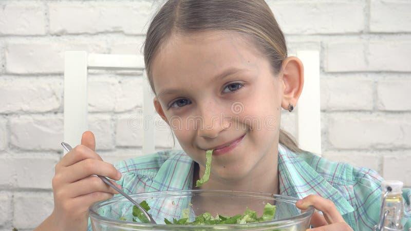 Το παιδί που τρώει την πράσινη σαλάτα, παιδί στην κουζίνα, κορίτσι τρώει το φρέσκο λαχανικό, υγιή τρόφιμα στοκ φωτογραφίες