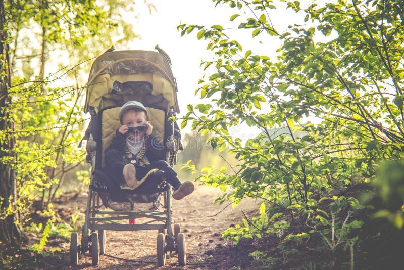 Το παιδί στον περιπατητή μωρών αναπηδά υπαίθρια στοκ φωτογραφία