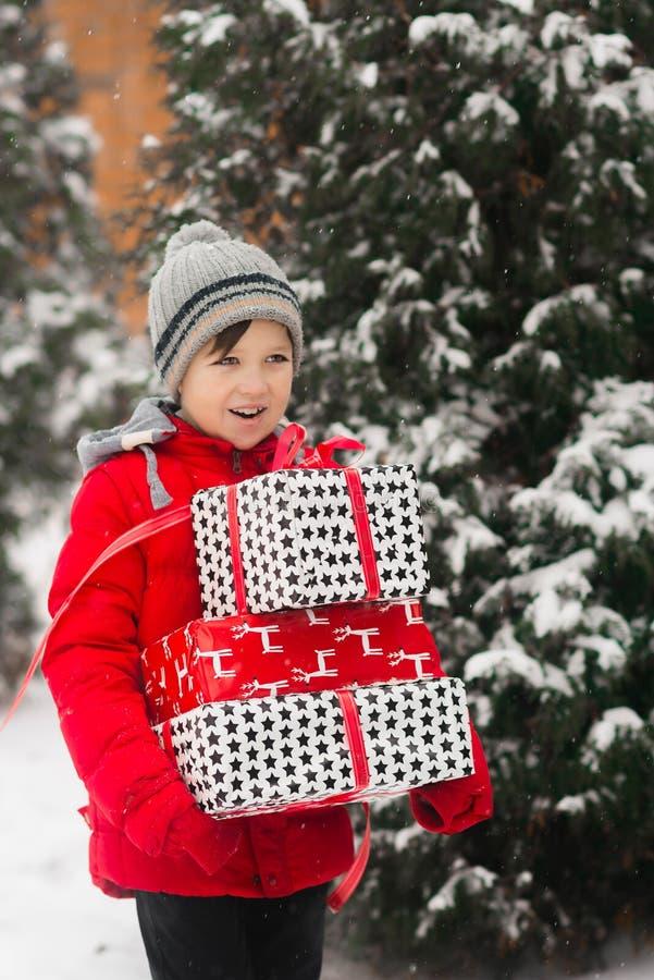 Το παιδί φέρνει τα δώρα στα χέρια του Το αγόρι φέρνει το πακέτο κιβωτίων στοκ εικόνα με δικαίωμα ελεύθερης χρήσης