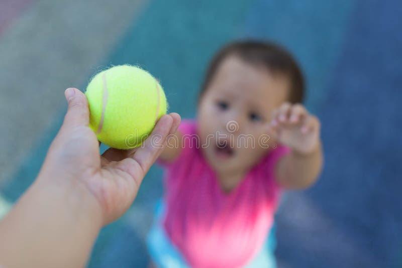 Το παιδί φθάνει για τη σφαίρα αντισφαίρισης από το δάσκαλο στοκ φωτογραφία