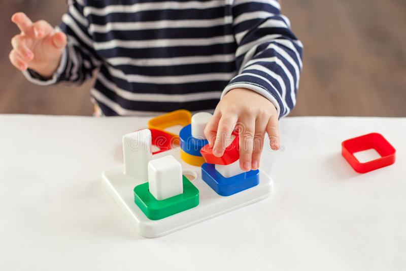 Το παιδί 1.5 χρονών που κάθεται στον πίνακα και που παίζει με ένα αναπτυσσόμενο παιχνίδι, τεχνική Montessori, τα χέρια παιδιών `  στοκ φωτογραφία με δικαίωμα ελεύθερης χρήσης