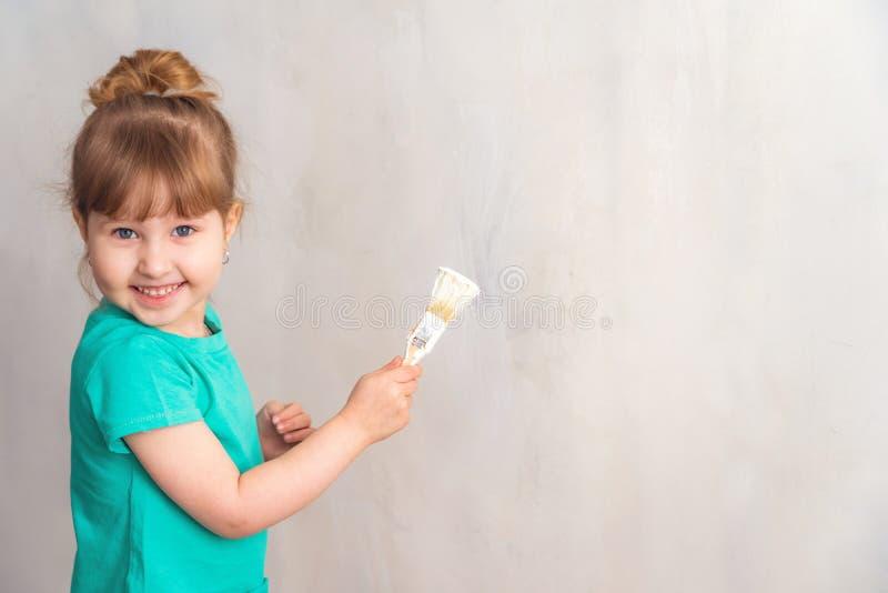 Το παιδί χρωματίζει τον τοίχο με μια άσπρη βούρτσα χρωμάτων η εργασία λήξης στις εγκαταστάσεις του καλλιτέχνη χρωματίζει τους τοί στοκ φωτογραφία