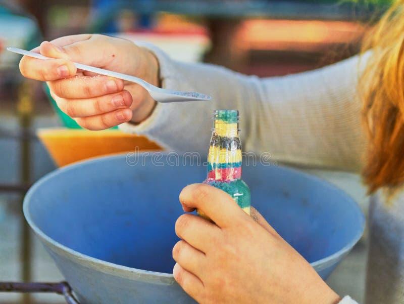 Το παιδί χύνει τη χρωματισμένη άμμο στο μπουκάλι στοκ φωτογραφίες