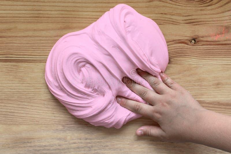 Το παιχνίδι για slime παιδιών το χέρι των παιδιών ζυμώνει τη μάζα του ροζ στοκ φωτογραφίες