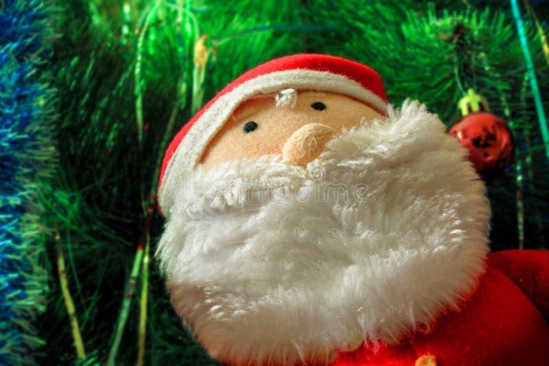 Το παιχνίδι διακοσμήσεων Άγιου Βασίλη κάθεται κάτω από το χριστουγεννιάτικο δέντρο r στοκ εικόνα