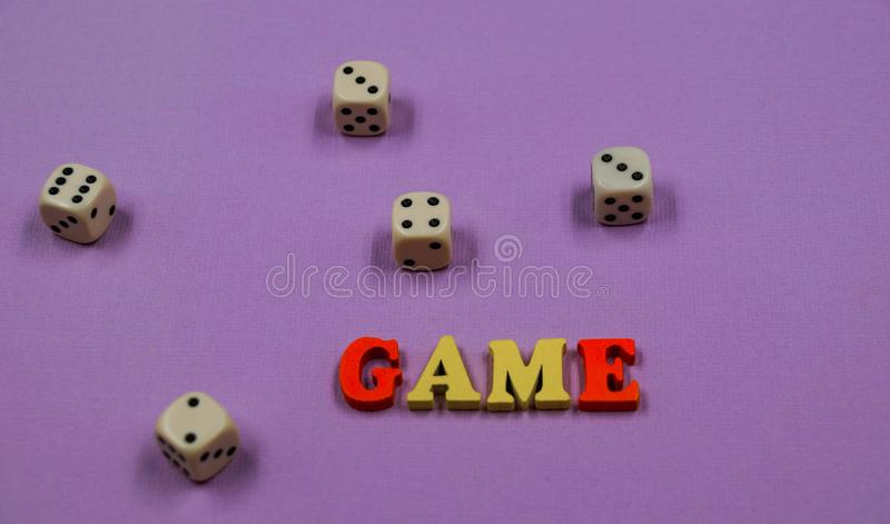Το παιχνίδι ` λέξης ` αποτελείται από τις πολύχρωμες ξύλινες επιστολές και το παιχνίδι χωρίζει σε τετράγωνα σε ένα ρόδινο υπόβαθρ στοκ φωτογραφία με δικαίωμα ελεύθερης χρήσης