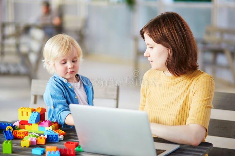 Το παιχνίδι μικρών παιδιών με την κατασκευή εμποδίζει ενώ η μητέρα του που εργάζεται στον υπολογιστή στοκ φωτογραφίες