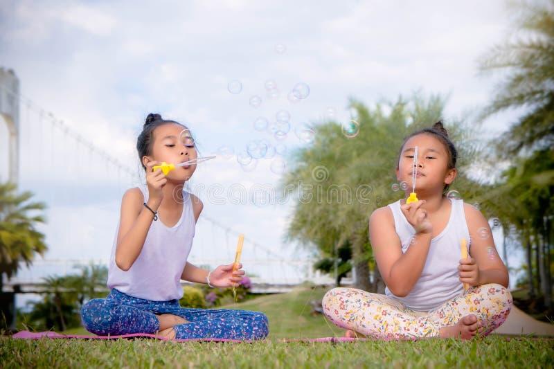 Το παιχνίδι Girs και απολαμβάνει τις φυσαλίδες χτυπήματος δραστηριοτήτων στο πάρκο, φιλία στην ημέρα παιδιών ` s στοκ εικόνα