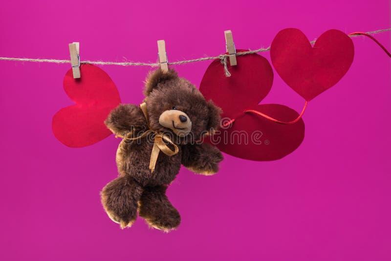 Το παιχνίδι Teddy αντέχει με τις καρδιές εγγράφων αναστέλλεται από το σχοινί clothespins σε ένα υπόβαθρο των άσπρων σύννεφων κινο στοκ εικόνα