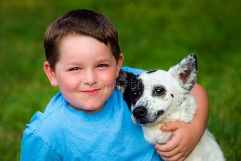 Το παιδί αγκαλιάζει στοργικά το κατοικίδιο ζώο του στοκ φωτογραφία