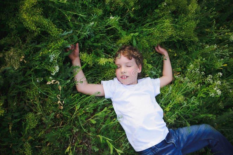 Το παιδί βρίσκεται στη χλόη και να ονειρευτεί στοκ φωτογραφία