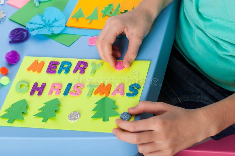 Το παιδί κάνει μια κάρτα Χριστουγέννων στοκ φωτογραφίες