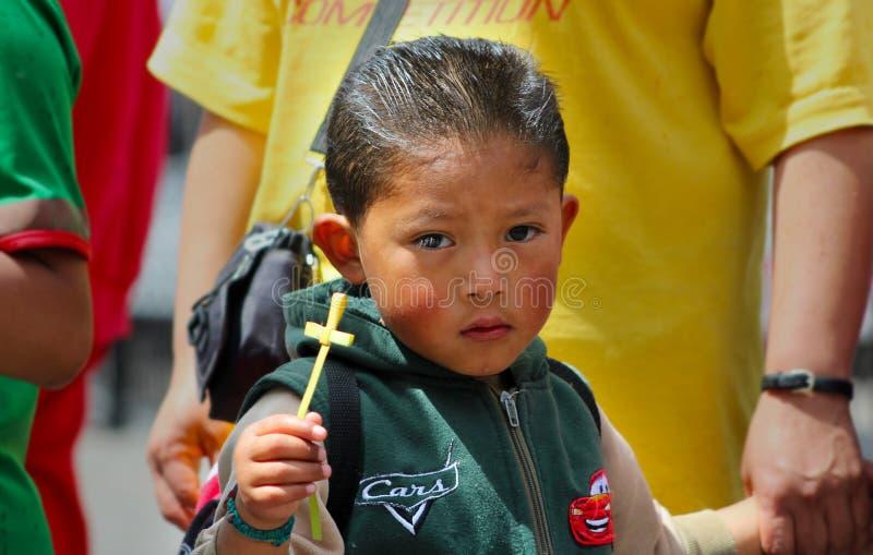 Το παιδί κρατά ένα στρέμμα αχύρου σε μια θρησκευτική τελετή στοκ εικόνες