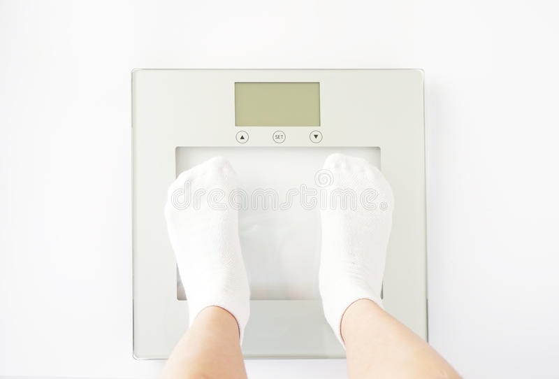Το παιδί μετρά το βάρος στις κλίμακες στοκ εικόνα με δικαίωμα ελεύθερης χρήσης