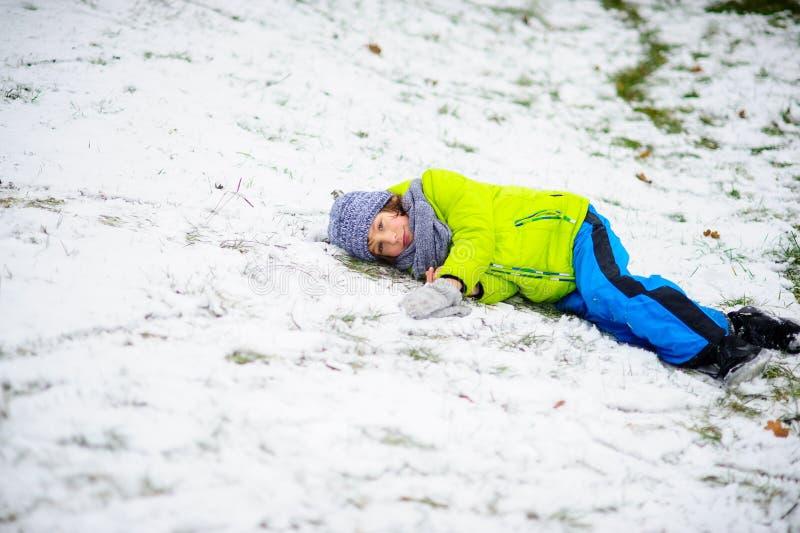 Το παιδί σε ένα φωτεινό κοστούμι σκι βρίσκεται μόνο στο χιόνι στοκ εικόνα