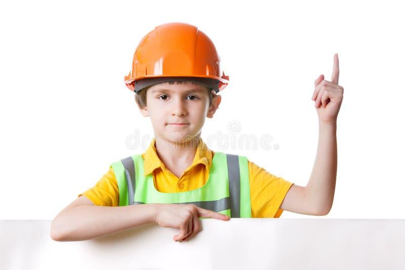 Το παιδί στα ενδύματα εργασίας με τον πίνακα διαφημίσεων κρατά το δάχτυλο επάνω στοκ φωτογραφία με δικαίωμα ελεύθερης χρήσης
