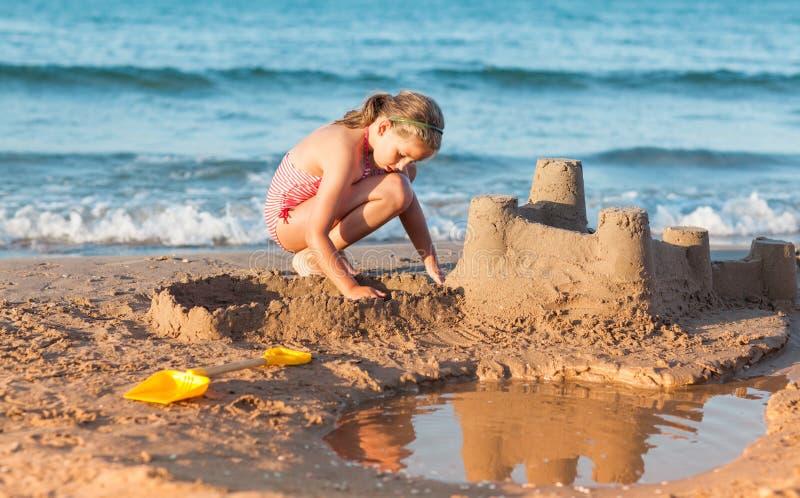 Το παιδί στηρίζεται sandcastle στην παραλία στοκ φωτογραφία με δικαίωμα ελεύθερης χρήσης