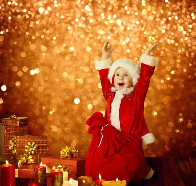 Το παιδί Χριστουγέννων, ευτυχές παιδί παρουσιάζει τα δώρα, κόκκινη τσάντα Santa, όπλα αγοριών επάνω στοκ φωτογραφίες