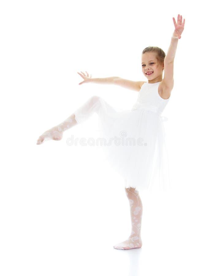 Το παιδί Ballerina αύξησε το πόδι της επάνω και τραβώντας την κάλτσα στοκ φωτογραφίες