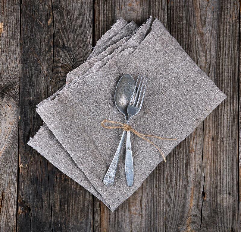 το παλαιά δίκρανο και το κουτάλι μετάλλων έδεσαν με ένα καφετί σχοινί σε μια γκρίζα πετσέτα λινού στοκ εικόνες