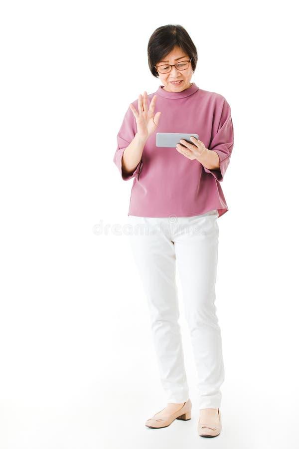 Το παλαιό ασιατικό κοίταγμα γυναικών στην οθόνη του smartphone και μοιάζει με την αίσθηση συγχέει και ανησυχεί Έννοια για την εκμ στοκ εικόνα