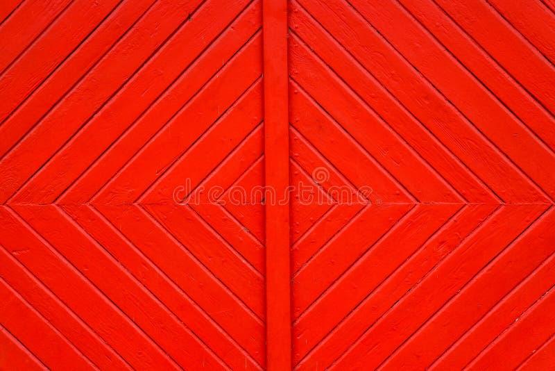 Το παλαιό βρώμικο και ξεπερασμένο κόκκινο πορτοκάλι χρωμάτισε την ξύλινη λεπτομέρεια πορτών σανίδων τοίχων με τις διαγώνιες γραμμ στοκ φωτογραφία